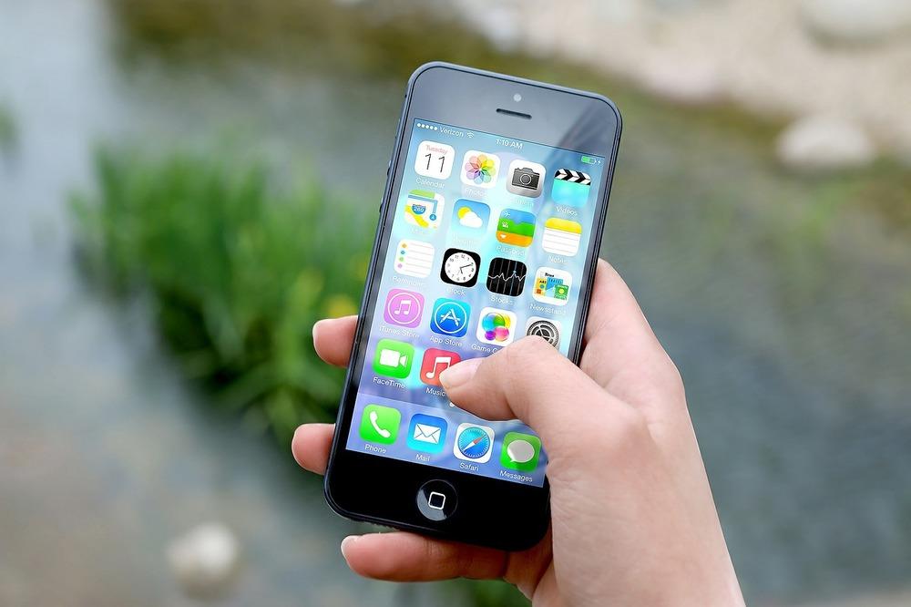 Mano sosteniendo celular con aplicaciones.