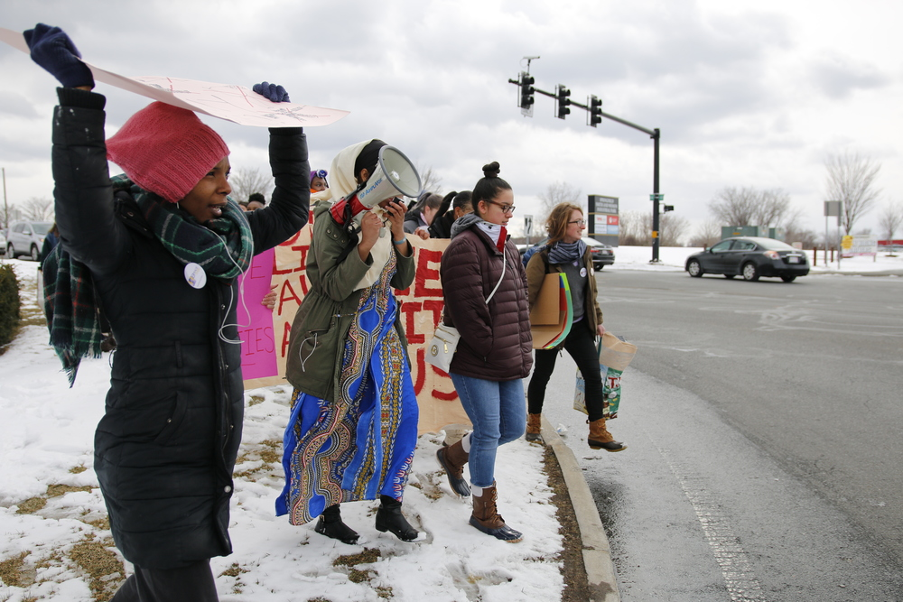 A multiracial group of dmonstrators holding up signs in the snow.