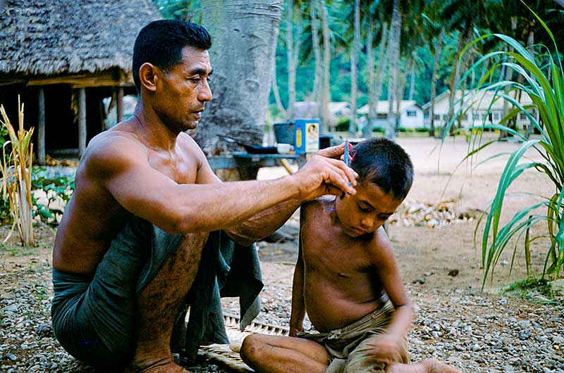The anthropologist's host cutting the hair of his son in Ofu, Manu'a Samoa 1955. Photo by Melvin Ember, HRAF President (1986-2009)